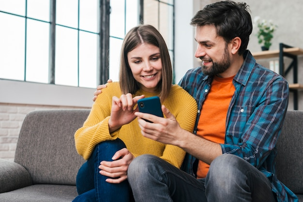 Young couple sitting together on sofa using mobile phone Free Photo