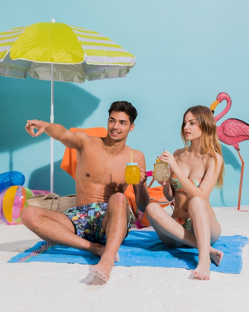 Young couple sitting on towel with cocktail in studio Free Photo