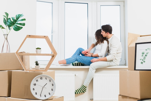 Young couple sitting on window sill looking through window with many cardboard boxes Free Photo