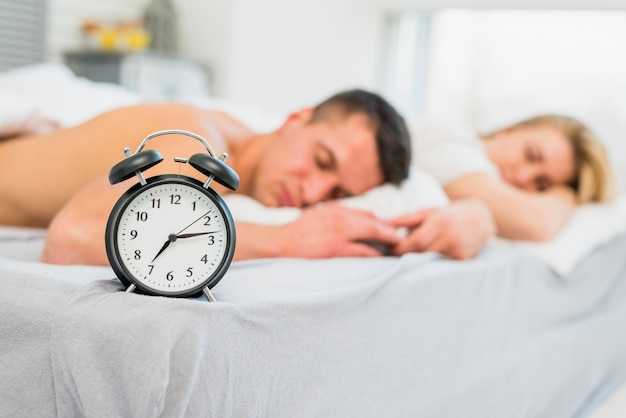 Young couple sleeping on bed near alarm clock Free Photo