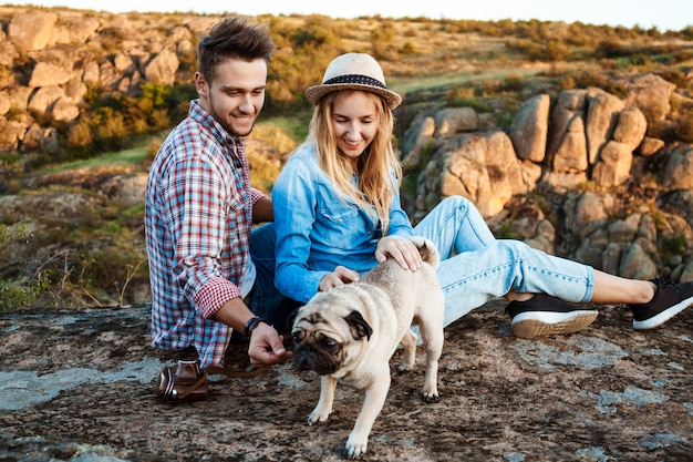 Young couple smiling, sitting on rock in canyon, stroking pug dog Free Photo