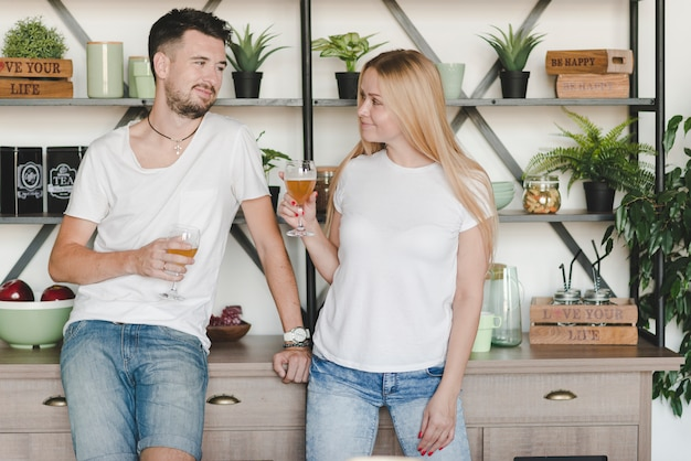Young couple standing in front of shelf holding glasses of beer Free Photo