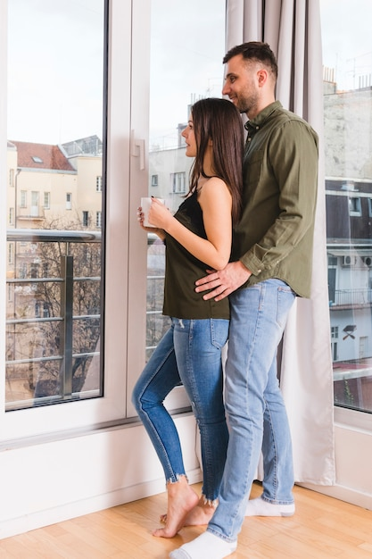 Young couple standing near the glass window Free Photo