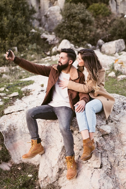 Young couple staying on a rock and taking a selfie Free Photo