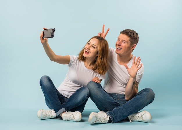 Young couple taking selfie on mobile phone against blue background Free Photo