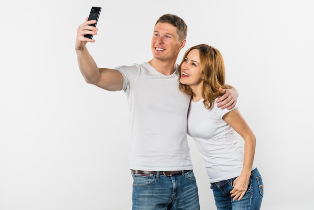 Young couple taking selfie on mobile phone isolated on white background Free Photo