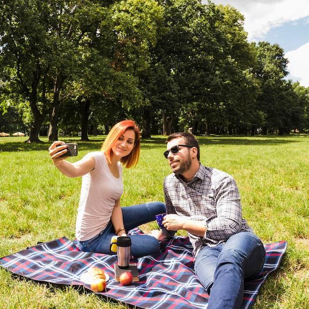 Young couple taking selfie on mobile phone at outdoor picnic Free Photo