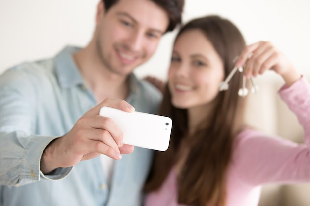 Young couple taking selfie using smartphone holding keys Free Photo