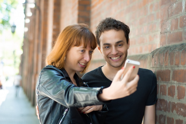 Young couple taking selfie with mobile phone outdoors. Premium Photo