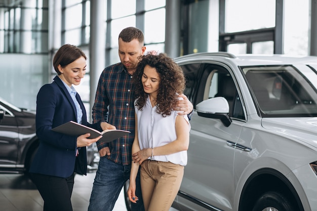 Young couple talking to a sales person in a car showroom Free Photo