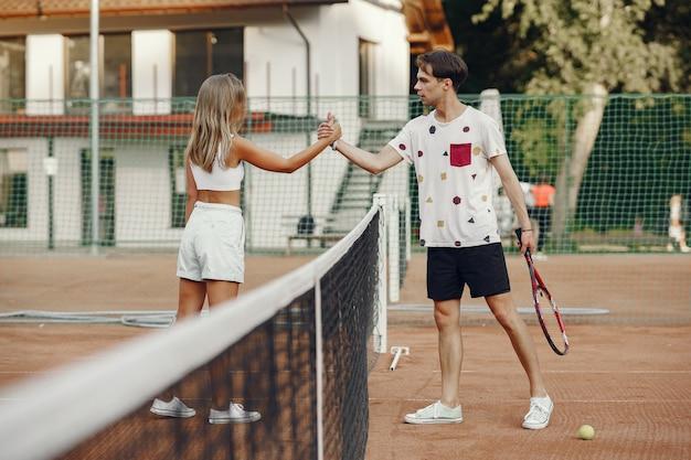 Coppia giovane sul campo da tennis. due giocatori di tennis in abiti sportivi. Foto Gratuite