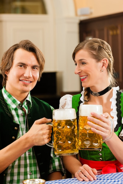 Young couple in traditional bavarian tracht in restaurant or pub Premium Photo