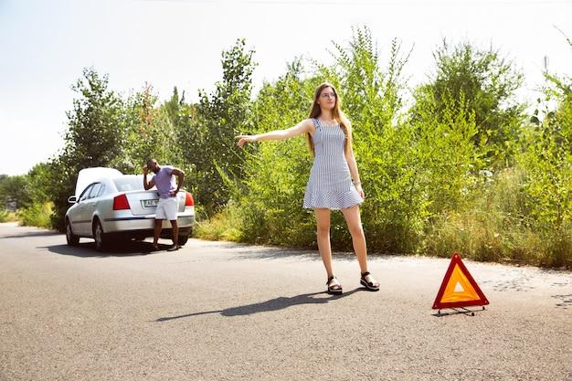 Молодая пара, путешествующая на машине в солнечный день Бесплатные Фотографии