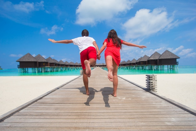 Young couple on tropical beach jetty at perfect island Premium Photo