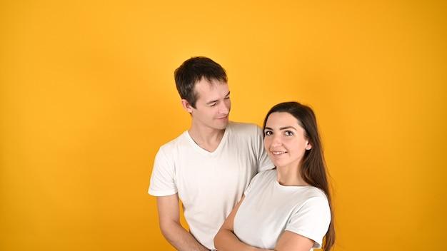 Молодая пара, двое друзей, парень, девушка в белых пустых пустых дизайнерских футболках, позируют изолированно на желтом Premium Фотографии