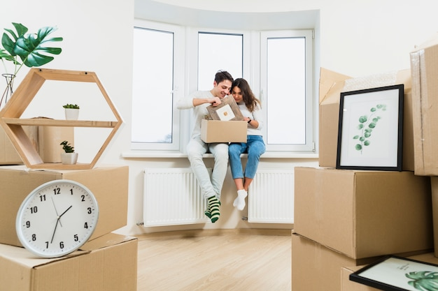 Young couple unpacking the cardboard boxes at their new house Free Photo