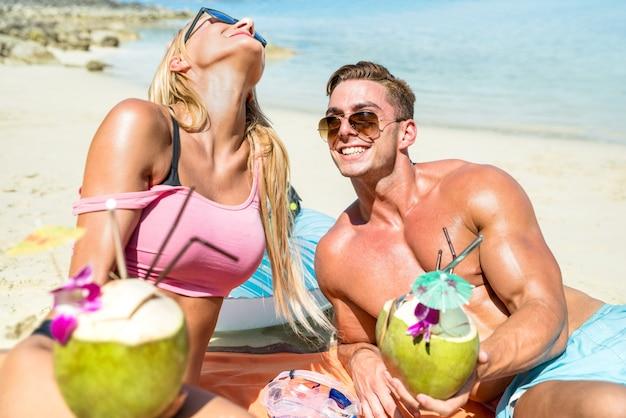 若いカップル行楽客ココナッツカクテルを飲むとプーケットタイの熱帯のビーチで楽しんで Premium写真