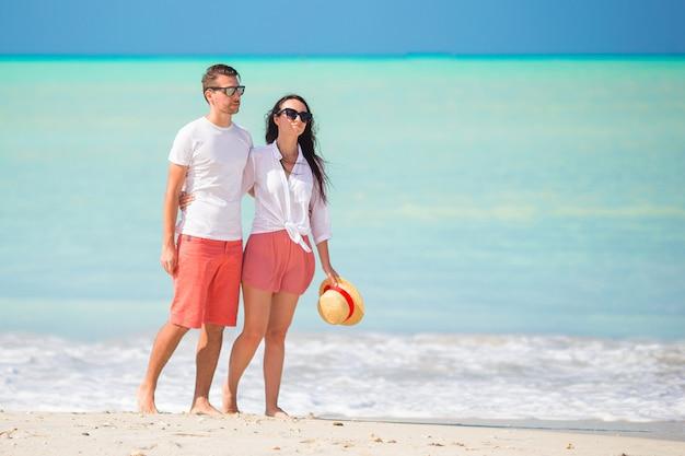カリブ海のアンティグア島で白い砂浜とターコイズブルーの海の水と熱帯のビーチを歩く若いカップル Premium写真