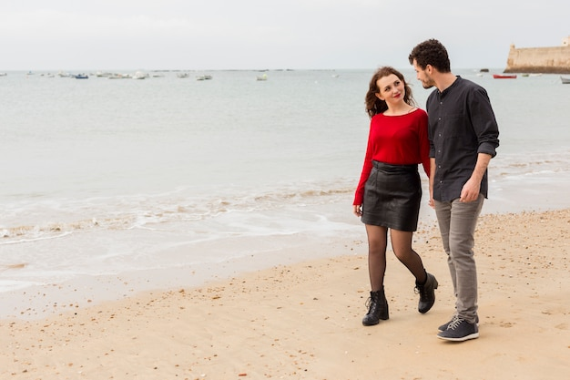 Young couple walking and talking on sea shore Free Photo