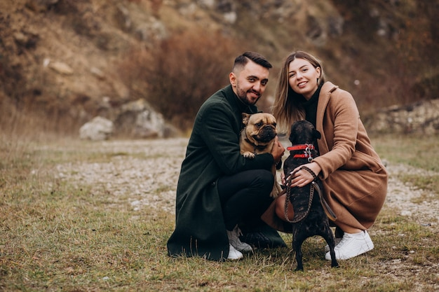 Young couple walking their french bulldogs in park Free Photo