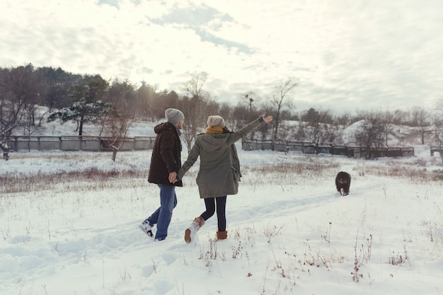 Young couple walking with a dog in a winter day Free Photo