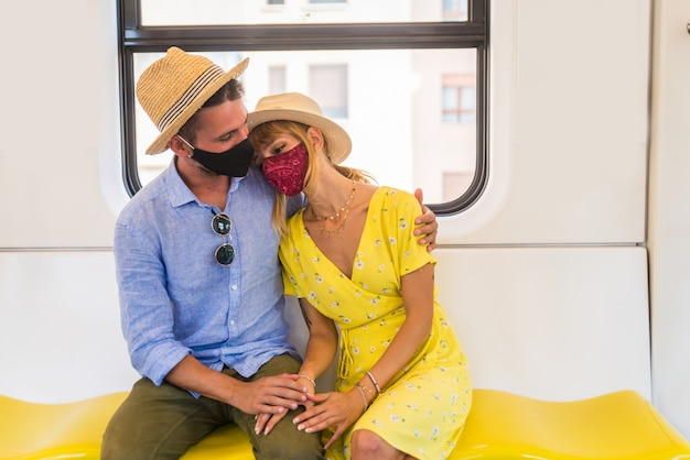 Young couple wearing face mask sitting on the train Premium Photo