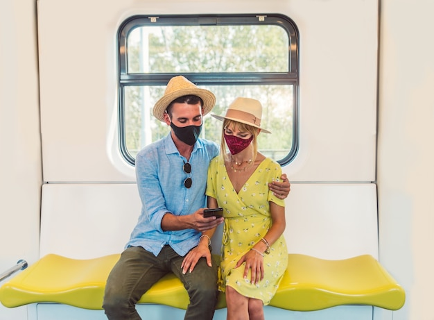Young couple wearing face mask using smart phone Premium Photo