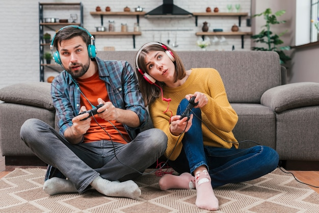 Young couple wearing headphone sitting on floor near the sofa playing the video game Free Photo
