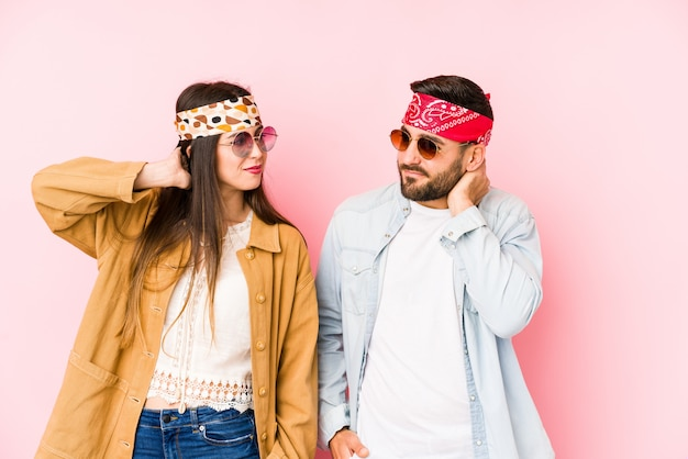 Young couple wearing a music festival clothes touching back of head, thinking and making a choice Premium Photo