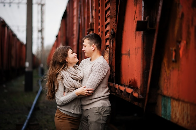 Young couple wearing on tied warm sweaters hugging in love at railway stations Premium Photo