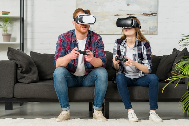 Young couple wearing virtual reality goggles playing the video game in the living room Free Photo
