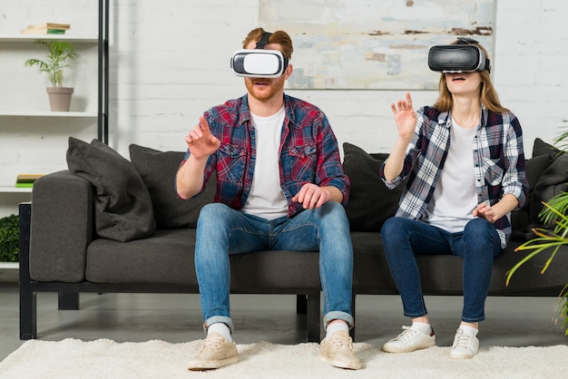 Young couple wearing virtual reality goggles touching in the air with hands Free Photo