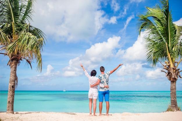 Young couple on white beach. happy family on honeymoon vacation Premium Photo