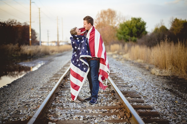 Coppia giovane con la bandiera americana sulle spalle in piedi sulla ferrovia Foto Gratuite
