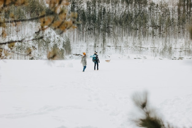 The young couple with dog haski at forest nature park in winter. travel adventure concept Premium Photo