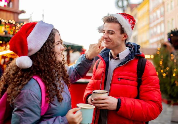 Young couple with drinks on christmas market in wroclaw, poland Premium Photo