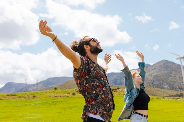 Young couple with hands up in nature Free Photo
