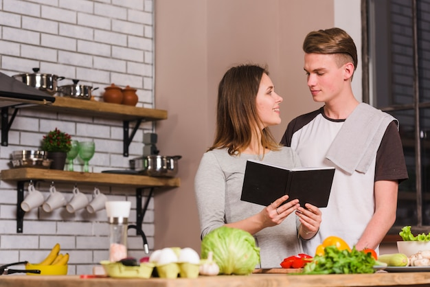 Young couple with notepad in kitchen Free Photo