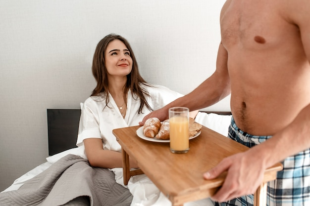 Young couple with romantic breakfast in the bed. happy beautiful woman is looking thankfully on her sweetheart Premium Photo