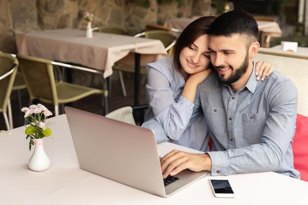 若いカップルが自宅で働いて、男と女が机に座って、屋内でラップトップに取り組んで Premium写真