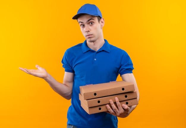青い制服と青い帽子をかぶって混乱した顔をして箱を持っている若い宅配便 無料写真