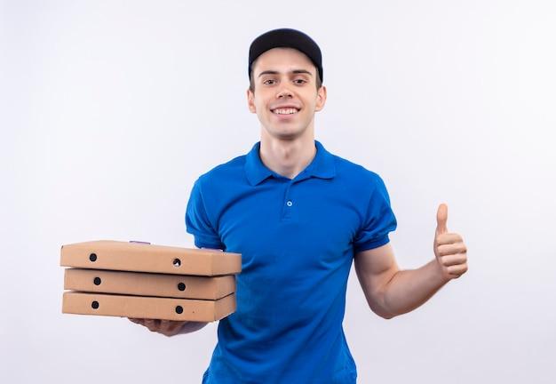 Молодой курьер в синей форме и синей кепке делает счастливый большой палец вверх и держит коробки Бесплатные Фотографии