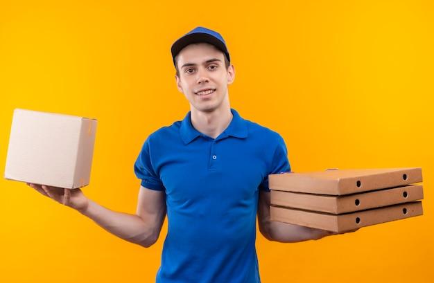 Молодой курьер в синей форме и синей кепке держит коробку слева и три коробки справа Бесплатные Фотографии