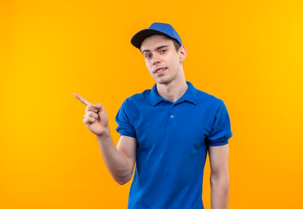 Молодой курьер в синей форме и синей кепке радостно показывает справа указательным пальцем Бесплатные Фотографии