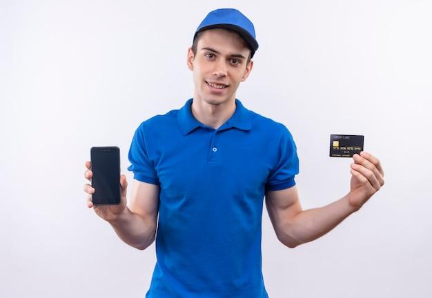 青い制服と青いキャップを身に着けている若い宅配便は、電話とカードを示しています 無料写真