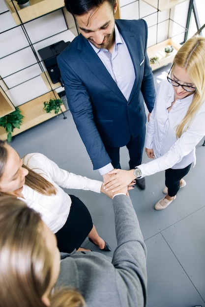 Young coworkers putting hands together as symbol of unity in the office Premium Photo