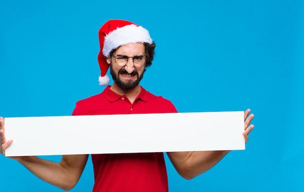 Молодой сумасшедший бородатый человек с шляпу санта. рождественская концепция Premium Фотографии