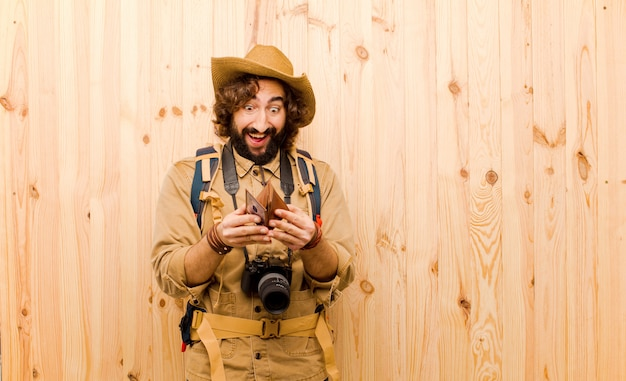 Young crazy explorer with straw hat and backpack on wood background Premium Photo