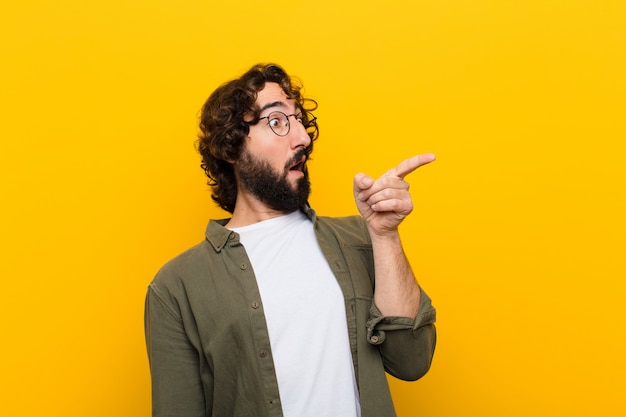 Young crazy man feeling shocked and surprised, pointing and looking upwards in awe with amazed, open-mouthed look against yellow wall Premium Photo