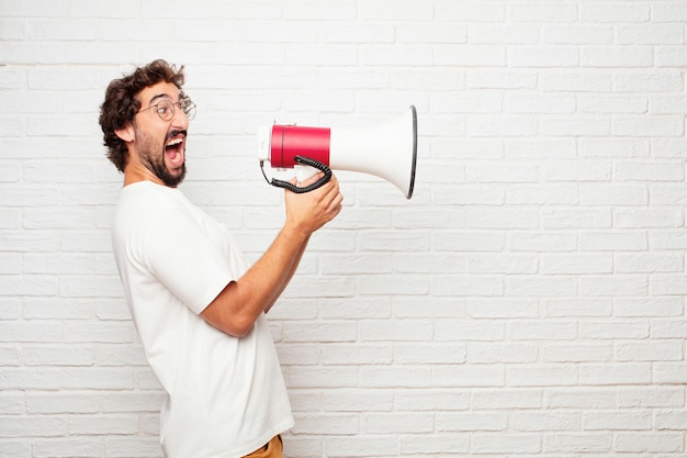 Young crazy man with a megaphone against brick wall. Premium Photo